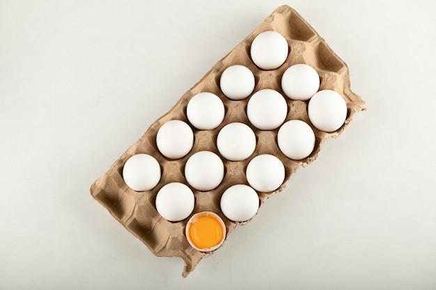 Œufs de poule crus dans une boîte à œufs sur une surface blanche.
