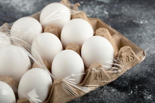 Œufs de poule crus dans une boîte à œufs sur une surface en marbre.