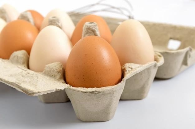 Oeufs de poule crus frais dans une boîte en carton, sur fond blanc. gros plan sur des œufs bruns et blancs.