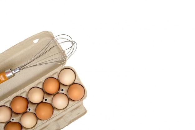 Oeufs de poule crus frais dans une boîte en carton, isolé sur fond blanc. la vue de dessus sur les œufs bruns et blancs.