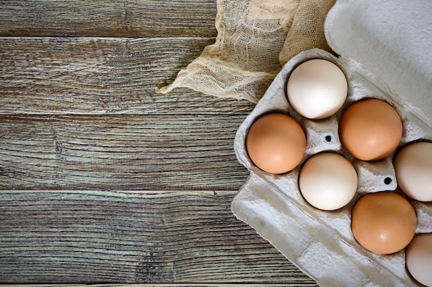 Oeufs de poule crus frais dans une boîte à œufs en carton sur fond de bois. la vue de dessus sur les œufs bruns et blancs.
