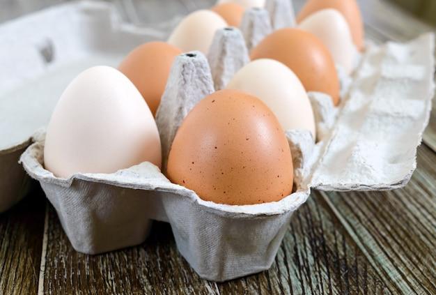 Oeufs de poule crus frais dans une boîte à œufs en carton sur fond de bois. vue rapprochée sur les œufs bruns et blancs.