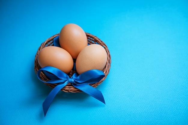Oeufs de poule dans un bol de paille avec un arc bleu sur fond bleu, fond.