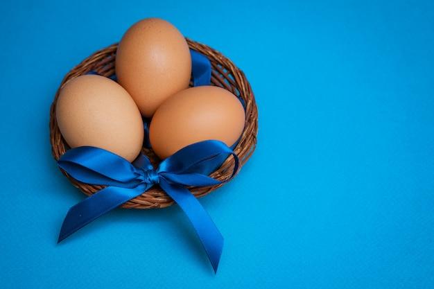 Oeufs de poule dans un bol de paille avec un arc bleu sur fond bleu,