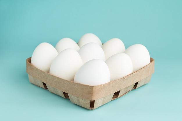 Œufs de poule dans un emballage en bois. neuf oeufs blancs dans une boîte