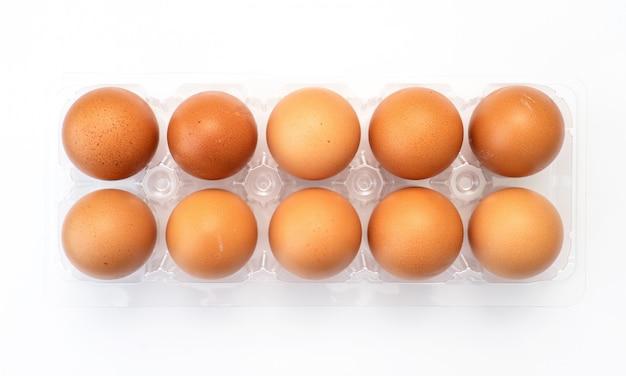 Œufs de poule dans un emballage en plastique sur fond blanc.