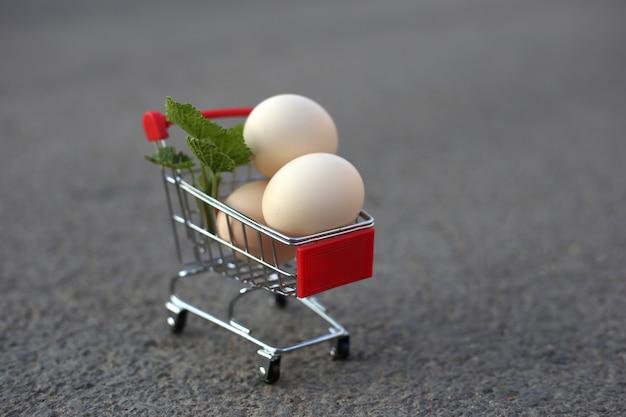 Oeufs de poule dans un mini chariot de supermarché sur la route.