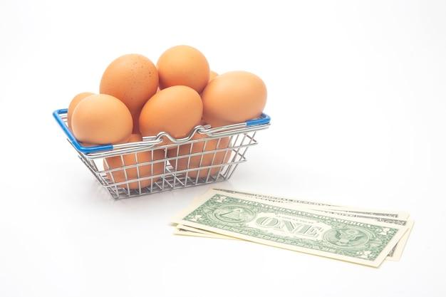 Œufs de poule dans un panier d'épicerie de supermarché et dollars sur fond blanc. vente et commerce de produits alimentaires