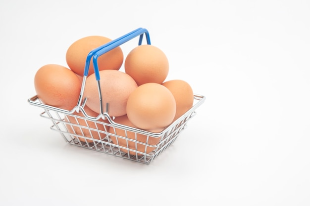Œufs de poule dans un panier d'épicerie de supermarché sur fond blanc.