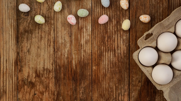 Oeufs de poule dans un plateau en carton et décor de pâques sur fond de bois