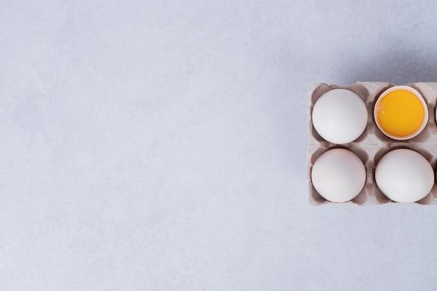Œufs de poule dans un récipient en papier sur une surface blanche.