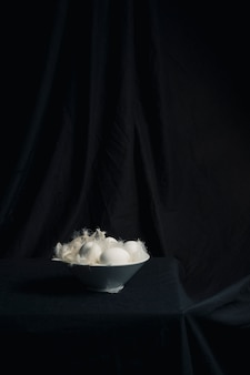 Œufs de poule entre les plumes dans un bol sur la table
