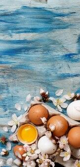Oeufs de poule et fleurs d'amandier sur fond de bois bleu