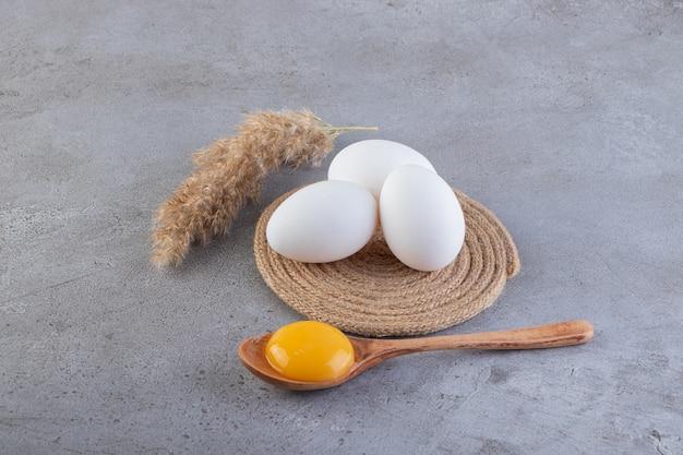Œufs de poule frais crus placés sur une surface en pierre.