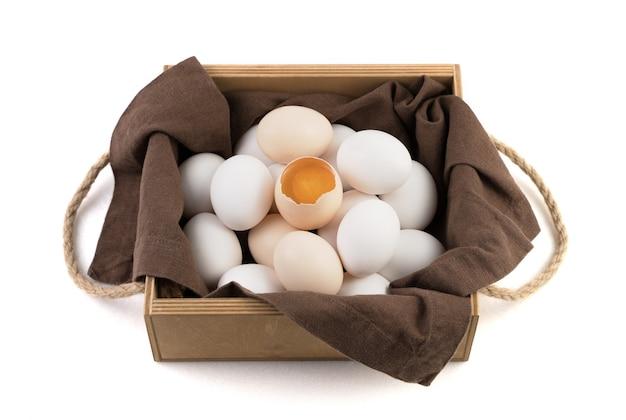 Les œufs de poule frais sont blancs et bruns avec un œuf cassé au centre où le jaune frais est visible.