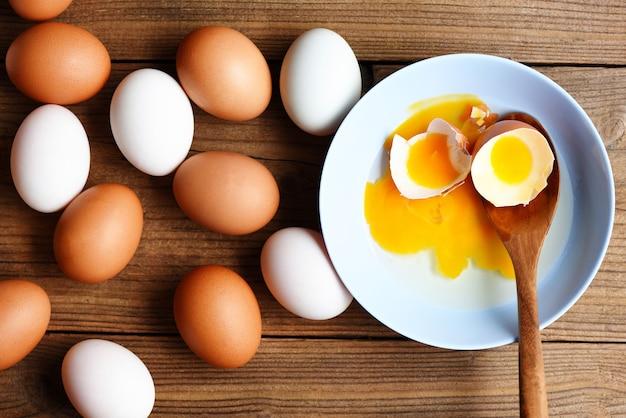 Oeufs de poule et oeufs de canard collectés à partir de produits agricoles naturels sur un concept d'alimentation saine en bois, jaune d'oeuf frais cassé