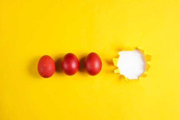 Oeufs de poule rouges sur une table en papier jaune avec un trou déchiré concept de pâques minimalisme