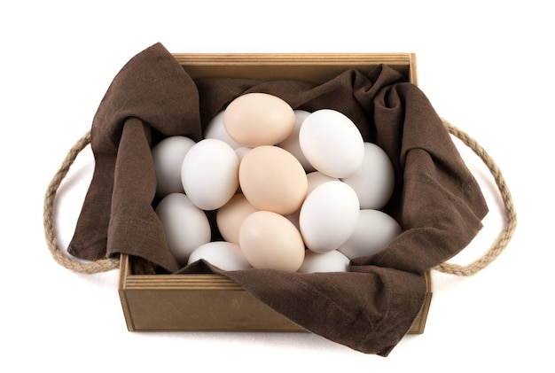 Les œufs de poule sont blancs et bruns dans un bel emballage en bois avec une serviette en lin marron.