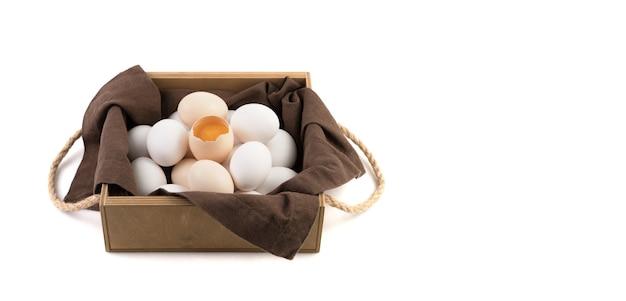 Les œufs de poule sont blancs et bruns avec un œuf cassé au centre, dans lequel un jaune frais est visible.