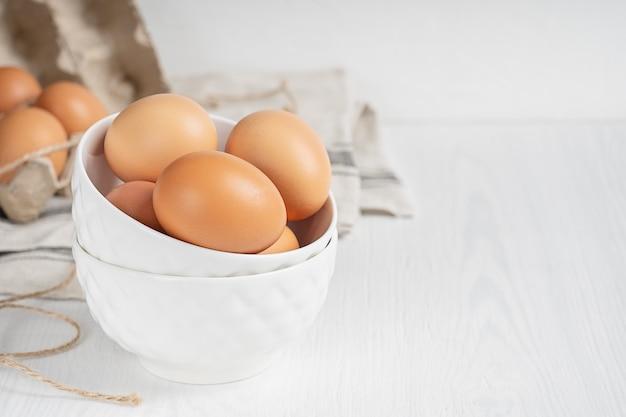 Oeufs de poulet bio brun cru dans des soucoupes en porcelaine et contenant de papier recyclé sur table en bois blanc
