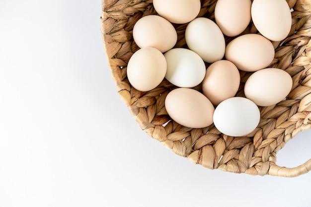 Oeufs de poulet bio de ferme crus frais dans un panier sur blanc