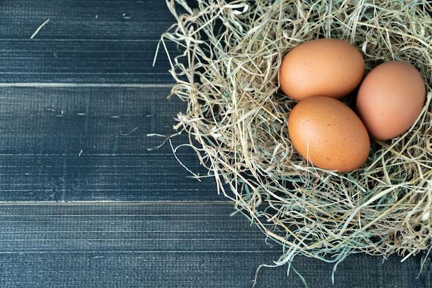 Œufs de poulet brun frais dans le nid de foin sur un fond en bois noir.
