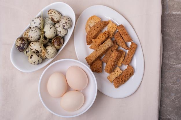 Œufs de poulet et de caille dans une tasse blanche avec des craquelins