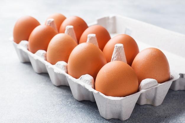 Oeufs de poulet cru brun dans des emballages d'usine sur fond gris.