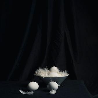 Œufs de poulet entre les plumes dans un bol