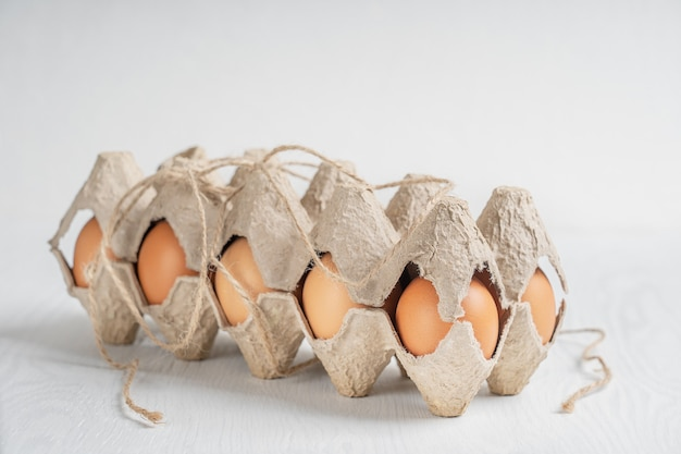 Oeufs de poulet frais brun cru dans un récipient en papier recyclé fermé sur fond de bois blanc