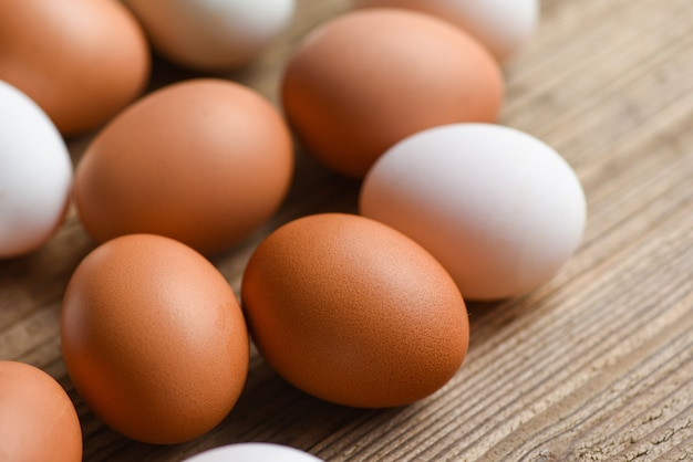 Oeufs de poulet frais et oeufs de canard sur table en bois / oeuf blanc et brun