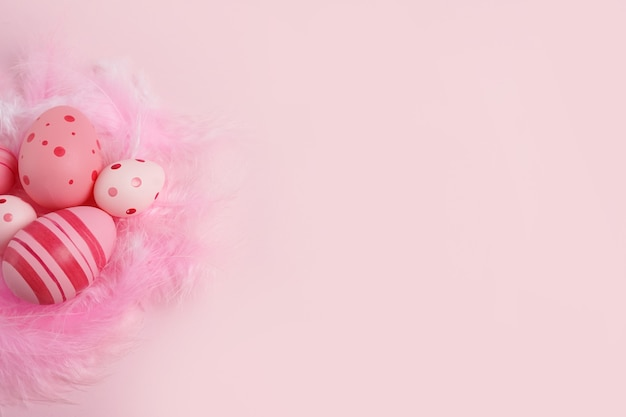 Oeufs roses avec des plumes sur fond rose, copiez l'espace