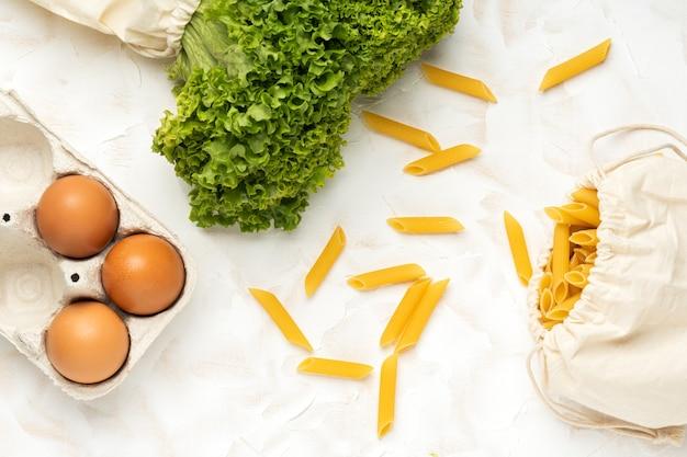 Oeufs, salade et pâtes en emballage écologique sur fond de ciment blanc. concept zéro déchet. achats alimentaires sans emballage. vue de dessus. mise à plat.