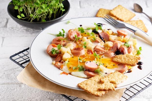 Oeufs avec saucisses, épices et roquette servis dans une assiette avec des craquelins