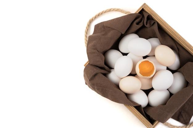 Les œufs sont blancs et bruns avec un œuf cassé au centre, dans lequel un jaune frais est visible.