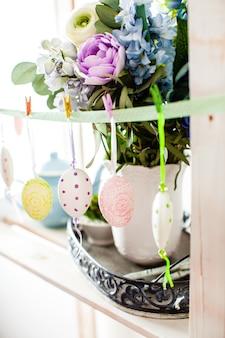 Oeufs suspendus au ruban - décorations de pâques sur l'étagère à l'intérieur