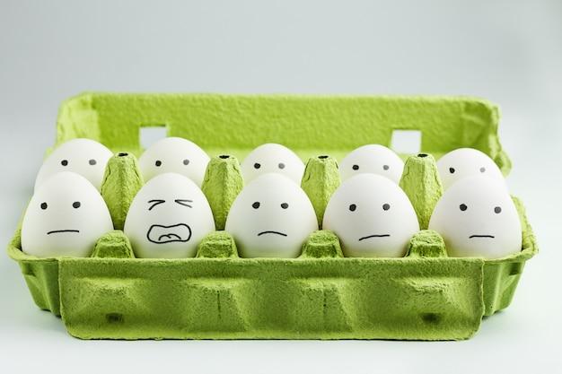 Oeufs avec des visages dessinés dans une boîte à œufs