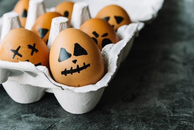 Oeufs avec visages d'halloween représentés dans un carton