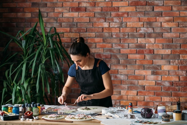 Oeuvre d'art en céramique en cours. inspiration parfum d'encens. jeune femme avec des outils de modélisation.