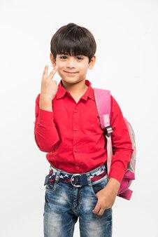 Off to school - mignon petit garçon indien ou asiatique en chemise rouge et jean denim avec sac d'école, debout isolé sur fond blanc