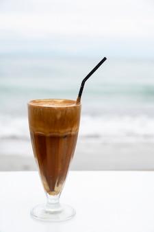 ? offee boire avec de la mousse et de la paille sur un tableau blanc avec mer