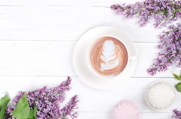 Сoffee avec latte art et guimauve sur table en bois blanc