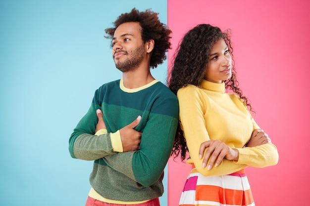 Offensé jeune couple debout avec les bras croisés