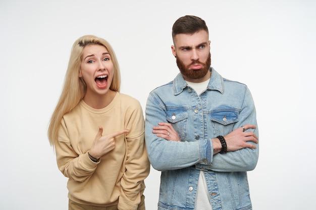 Offensé jeune homme barbu brune pliant ses mains sur la poitrine tandis que jolie femme blonde aux cheveux longs montrant avec enthousiasme sur lui avec la bouche grande ouverte, isolé sur blanc