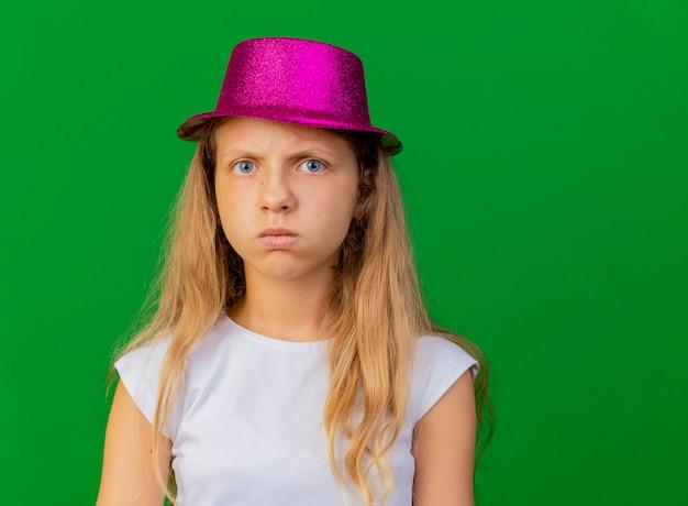 Offensé jolie petite fille au chapeau de vacances avec un visage sérieux