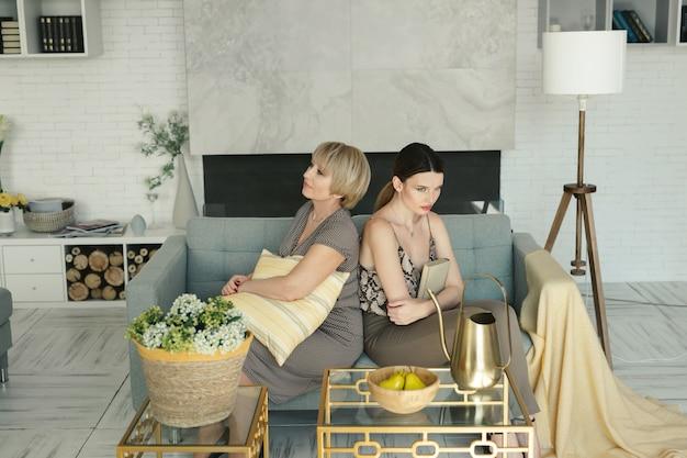 Offensé mère âgée et fille assise sur le canapé