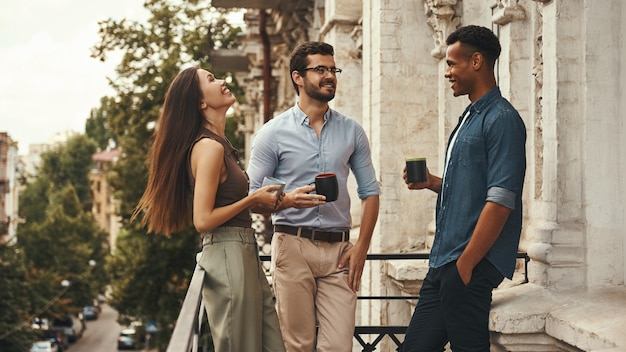 Office news jeunes collègues joyeux en tenue décontractée tenant des tasses et parlant entre eux