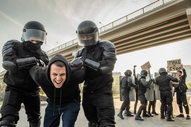 Officier anti-émeute dans des casques tordant les bras d'un manifestant agressif en pull à capuche tout en l'arrêtant dans la rue