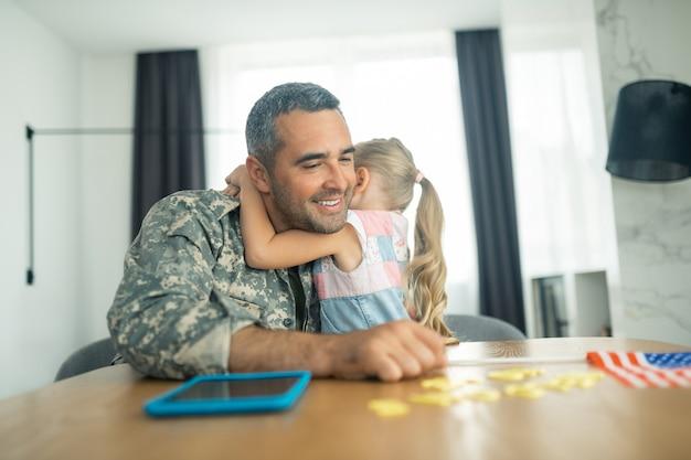 Officier émotif. beau officier militaire barbu se sentant émotif tout en serrant sa jolie fille mignonne dans ses bras