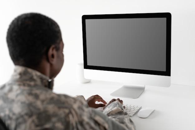 Officier militaire à l'aide de l'ordinateur de bureau